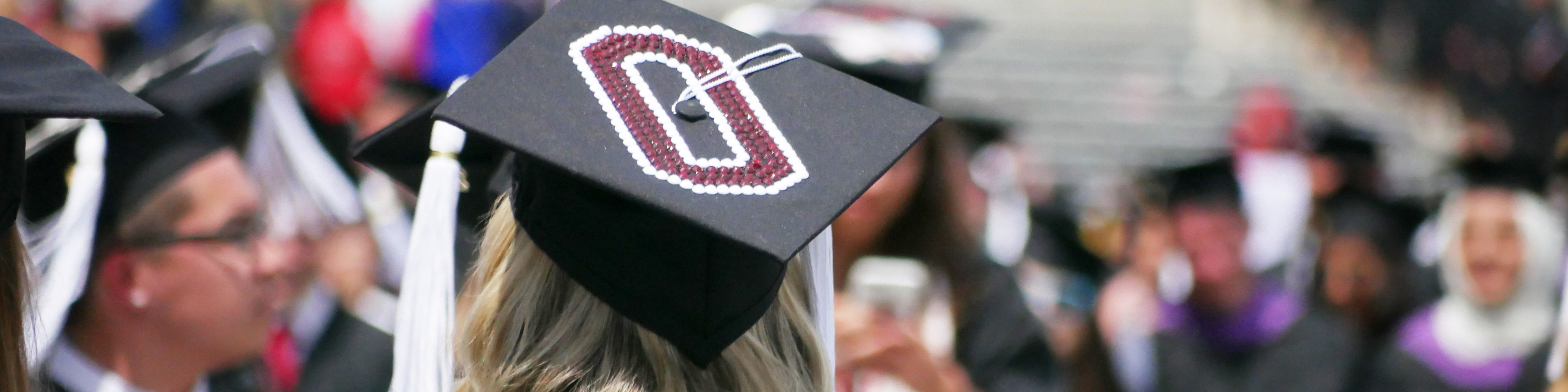 Woman at Spring Commencement wearing a graduation cap with Ohio State's Block 0.