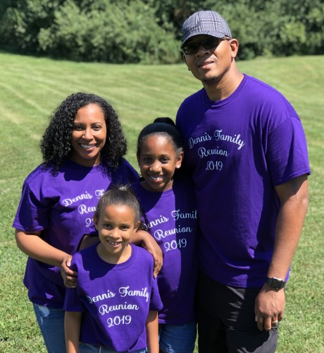 Joel, his wife and his daughters smile for a photo while wearing matching family reunion T-shirts.
