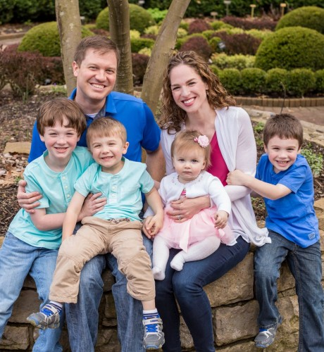 John, his wife, and their four children sit on a stone wall in a park and smile for a photo