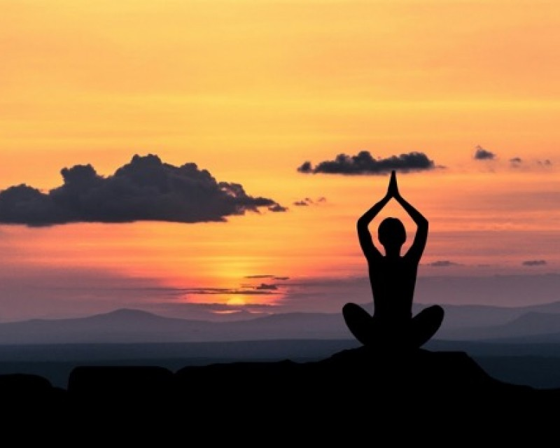 Person performing yoga in front of a sunset
