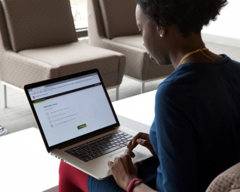 A woman sitting and using her laptop.