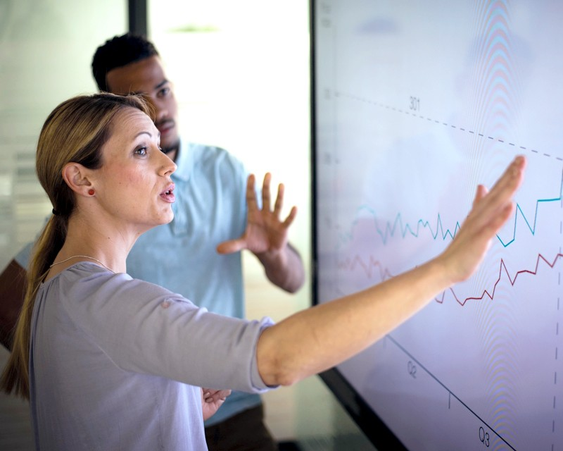 Two people reviewing a data chart