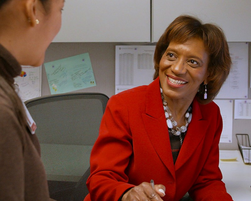 Woman talking with someone at her desk